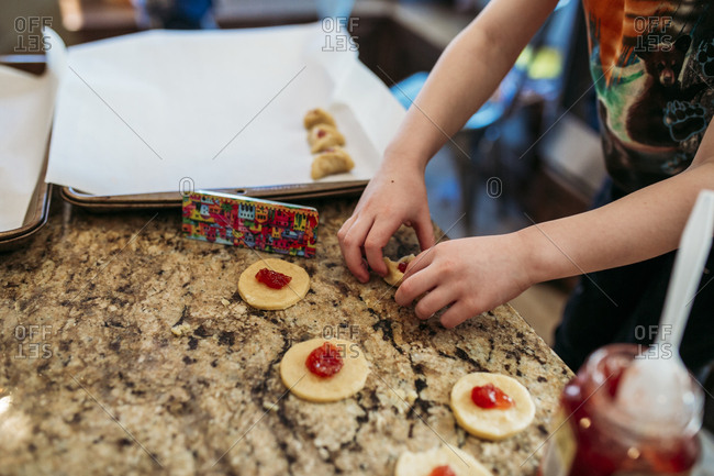 Child making traditional Jewish hamantaschen
