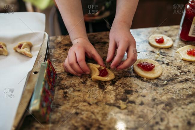 Child folding traditional Jewish hamantaschen