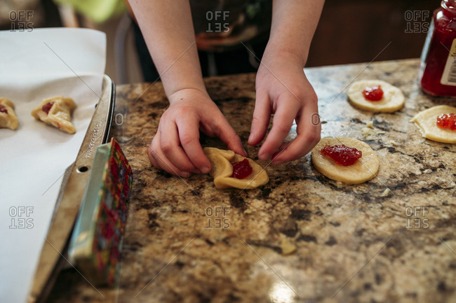 Child folding traditional Jewish hamantaschen