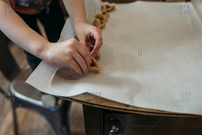 Child placing hamantaschen on a baking pan