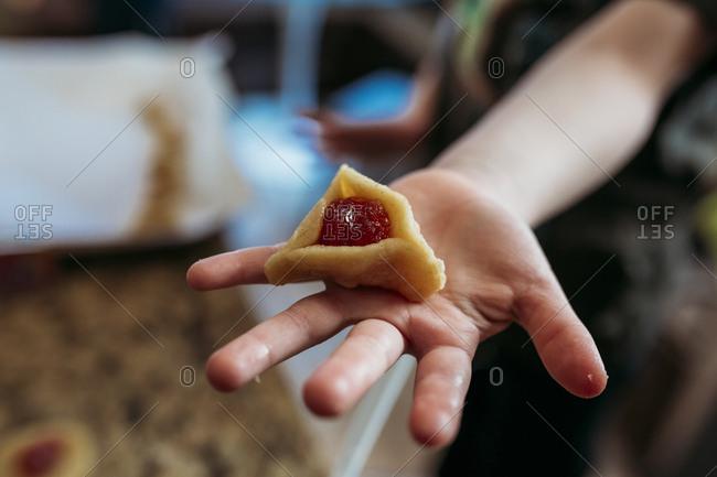 Child holding a traditional Jewish hamantaschen