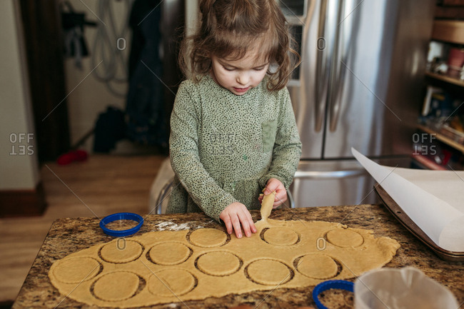 Girl cutting out dough while making hamantaschen