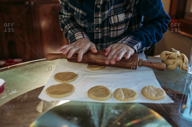 Boy rolling dough for hamantaschen