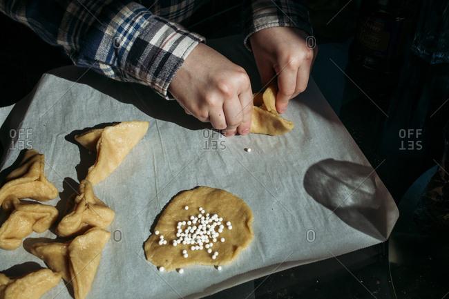 Boy folding hamantaschen cookies