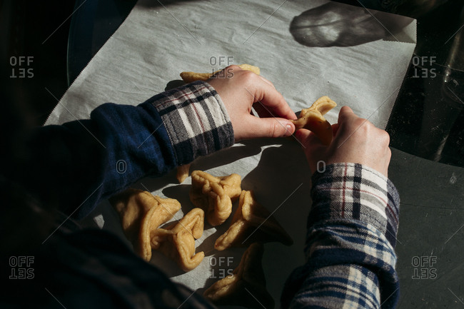 Overhead view of boy folding hamantaschen cookies