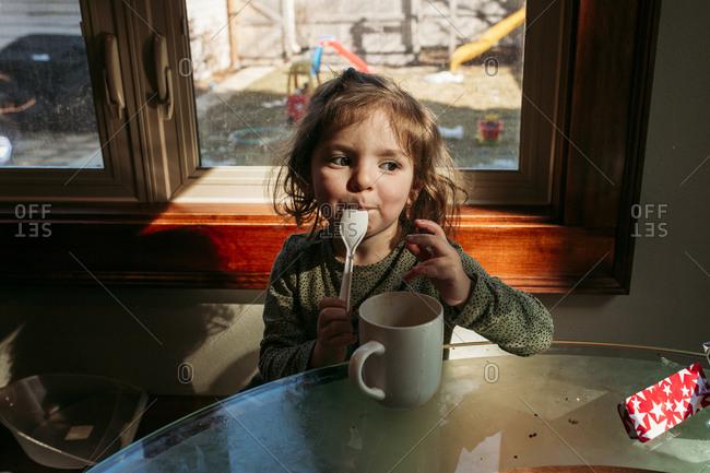 Little girl licking spoon