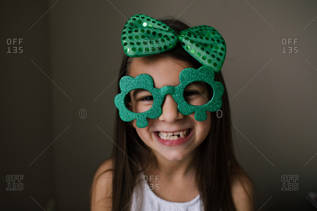 Girl wearing a green hair bow and clover glasses