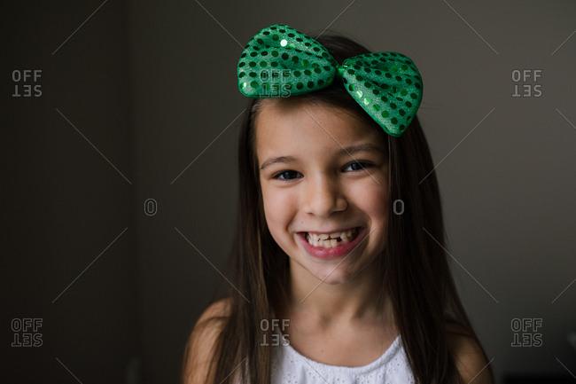 Girl with dark brown hair wearing a green hair bow
