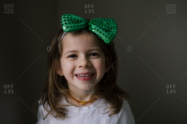 Happy girl wearing a green hair bow