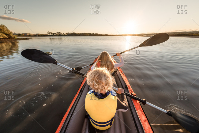 Little boy and sister paddling kayak on calm water at sunset
