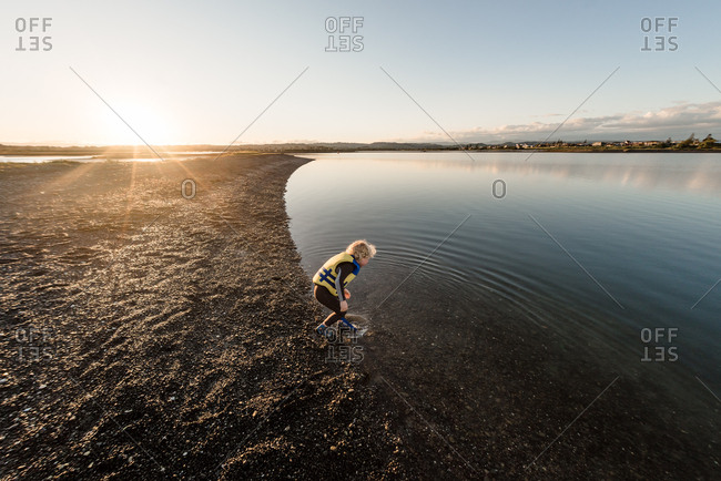 Young boy in wetsuit and lifejacket spotting something in shallows