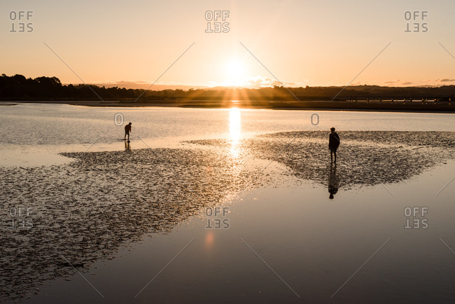 Children exploring the shallows silhouetted by setting sun