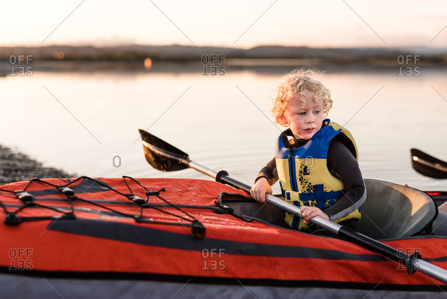 Little boy waiting in front seat of Kayak sunset