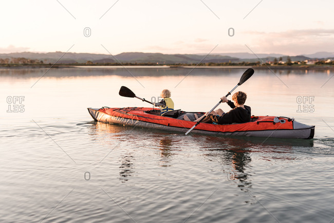 Little boy and older brother paddling kayak at sunset