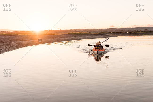 Little boy and older brother paddling kayak along shore at sunset