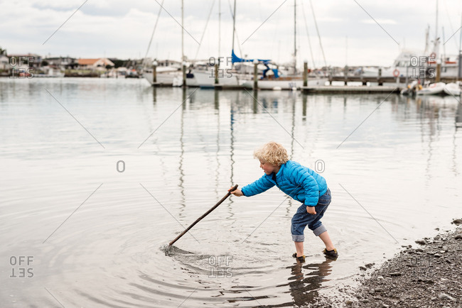 Little boy exploring the shallow water with a stick wetting his shoes