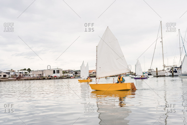 Young girl sailing  a small dinghy alone