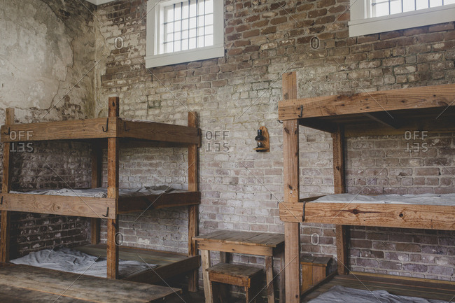Empty Jail Cell With Brick Walls And Wooden Bunkbeds Stock Photo