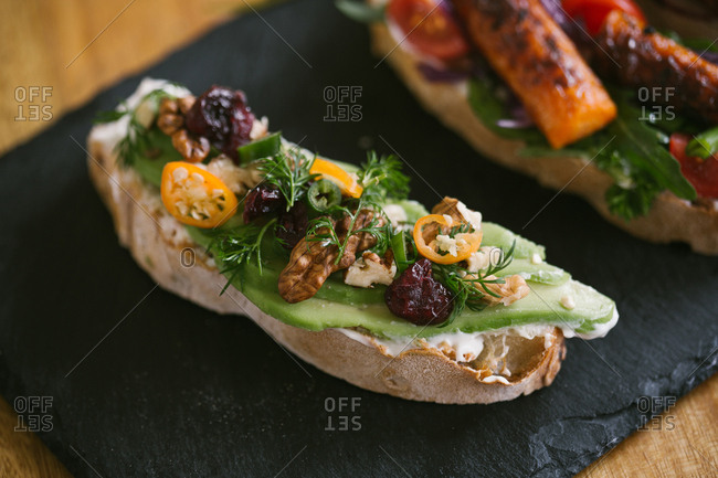 Bruschetta with cream cheese, avocado, fruit, and nuts
