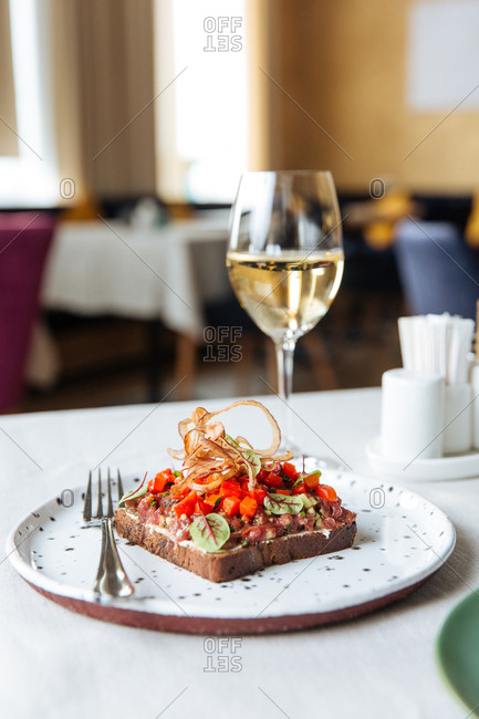 Bread with beef tartar and smoked paprika served with wine