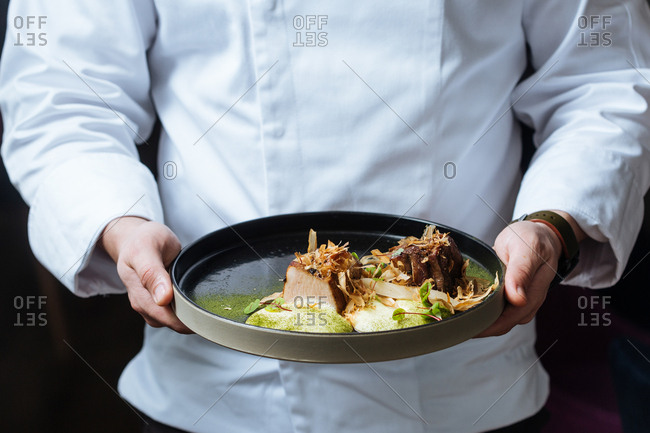 Chef holding pork belly dish