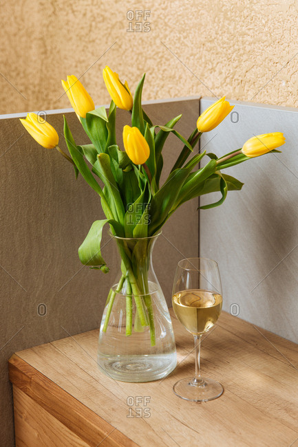 Yellow tulips in a vase beside a glass of wine