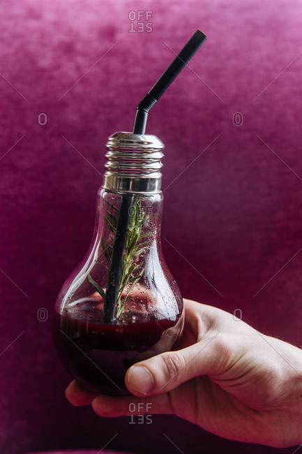 Hand holding a purple cocktail in a light bulb glass