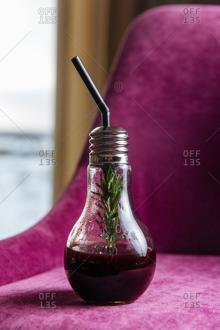 Purple cocktail in a light bulb glass