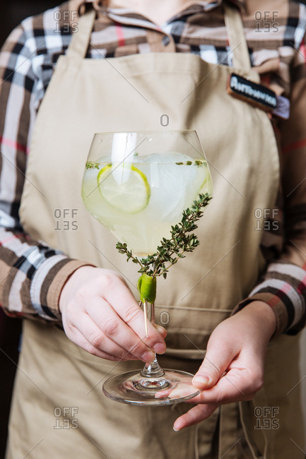 Waitress holding lemon and thyme cocktail
