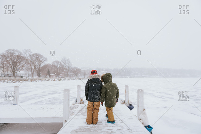 Two boys looking out at icy lake from dock in winter