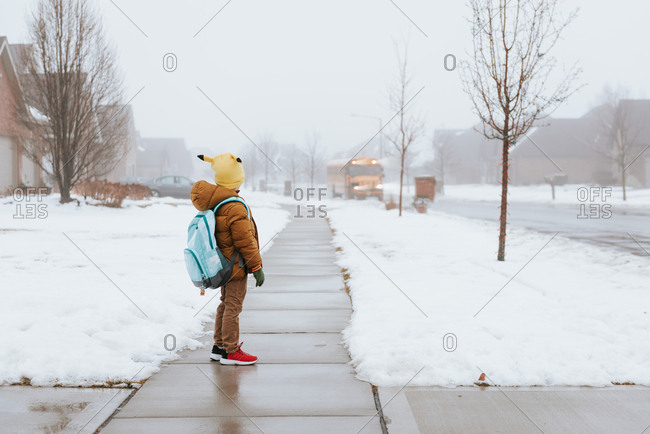 Boy walking towards bus on a winter day
