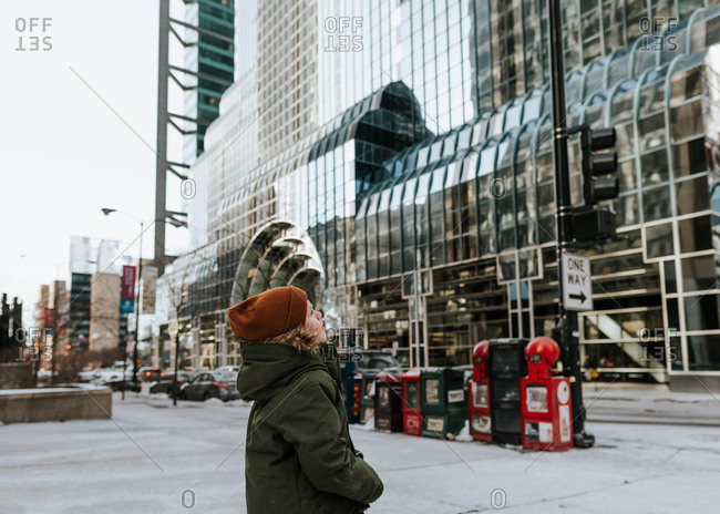 Boy looking up at a tall city building