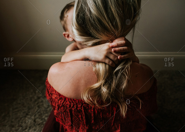 Little boy embracing mother with long blonde hair