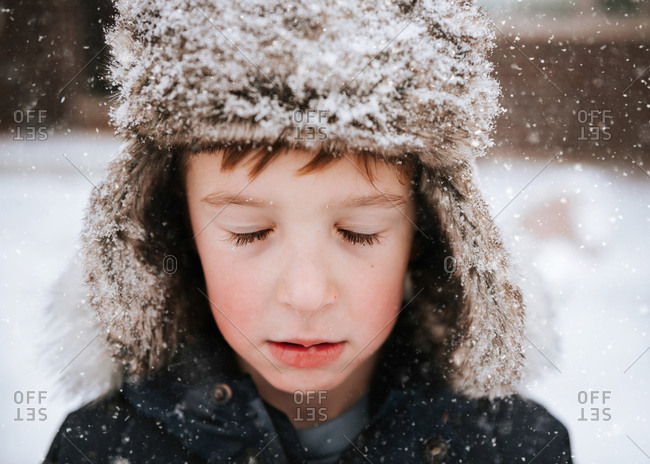 Portrait of a young boy with eyes closed during snowfall