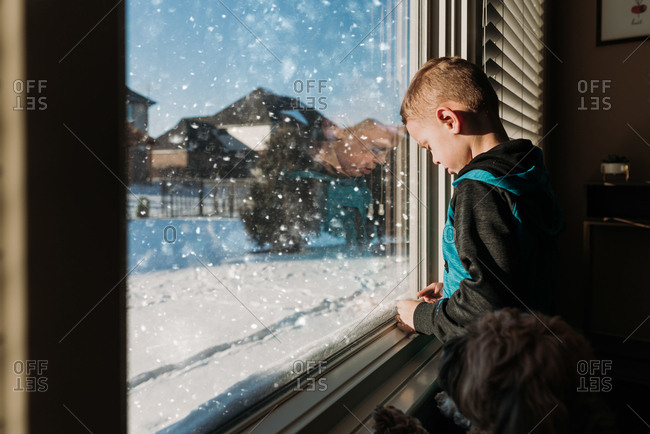 Boy looking out window with dog at snow