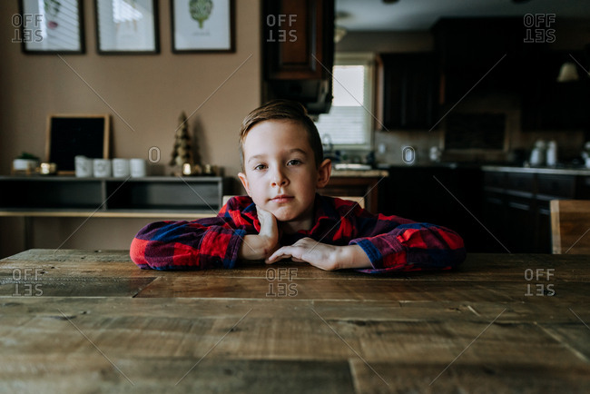 Young boy sitting at wooden table