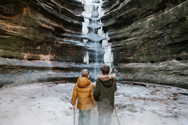 Rear view of boys looking at frozen waterfall in Starved Rock State Park