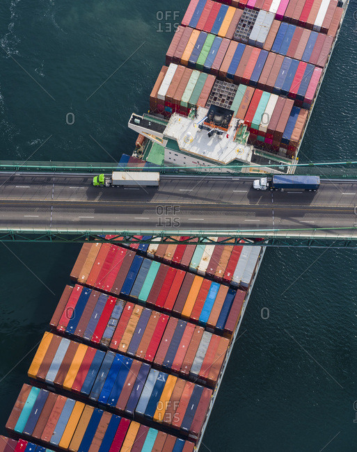 Large Container Ship crosses under a bridge at the port