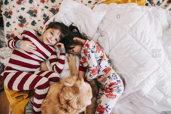 Two young kids cuddling on a bed with a dog