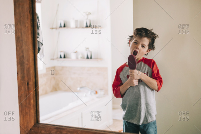 Little boy singing into hairbrush while looking in a mirror