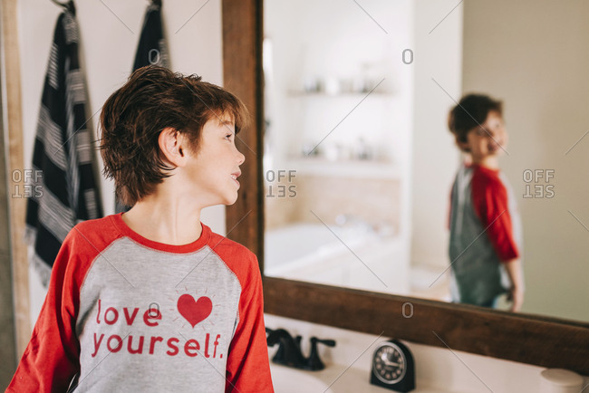 Little boy making faces at himself in a mirror