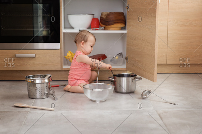 Baby sitting on floor with kitchenware