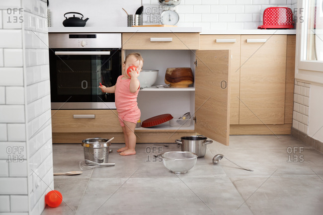Little baby making mess in kitchen with pots