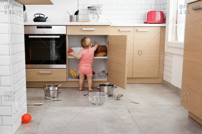 Little baby making mess of kitchen cabinets