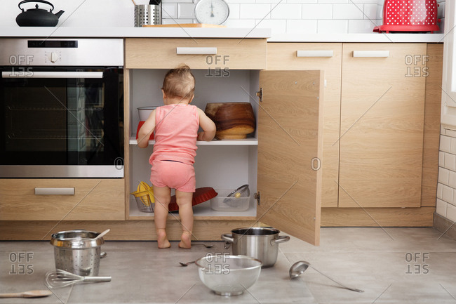 Rear view of baby making mess of kitchen cabinets