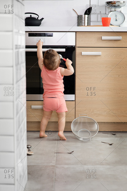 Little baby turning knob on oven in kitchen