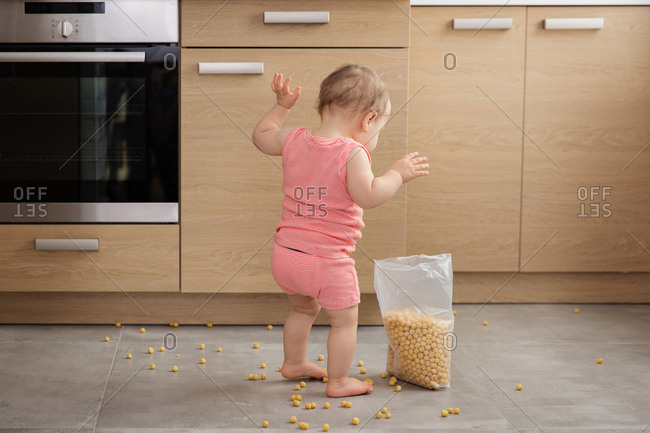 Baby making mess with bag of cereal