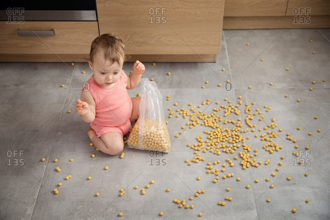 High angle view of baby making mess with bag of cereal