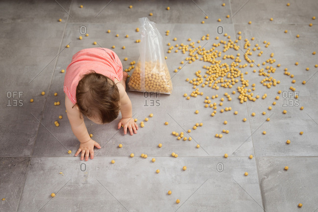 High angle view of baby crawling in spilled cereal