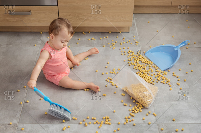 Baby sweeping up spilled bag of cereal